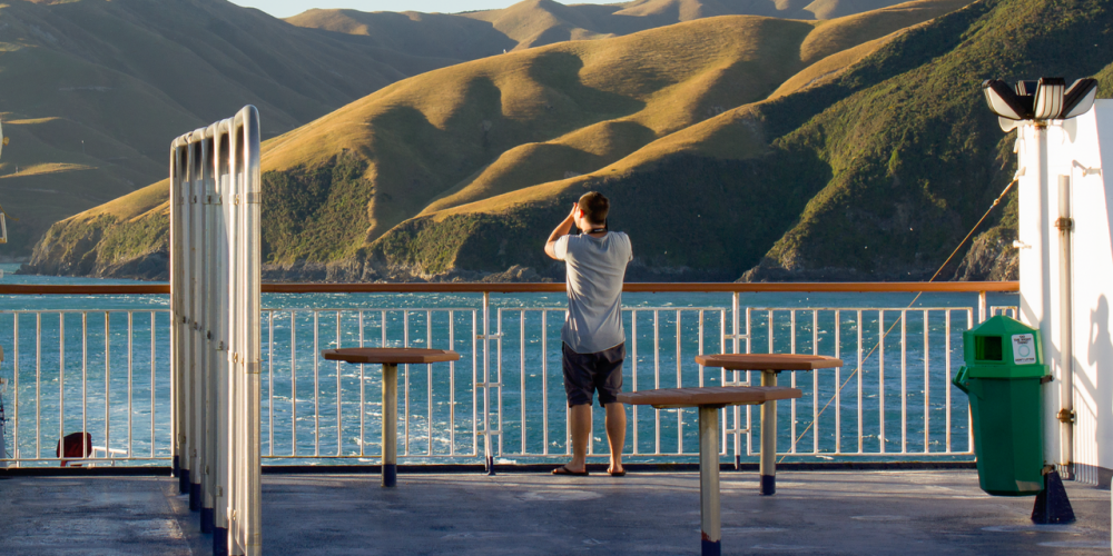 Interislander Aratere Man taking photo of Hills of East Head as ship leaves Tory Channel RH1500 Interislander